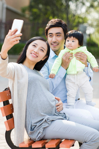 Happy young family taking self portrait with a smart phoneの写真素材 [FYI02226639]