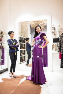 Chinese fashion designer examining dress on customerの写真素材 [FYI02226666]