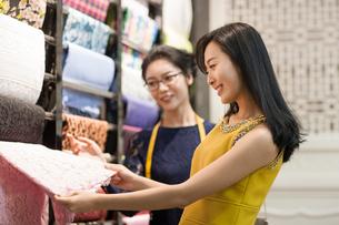 Chinese fashion designer helping customer choosing fabric swatchの写真素材 [FYI02226679]
