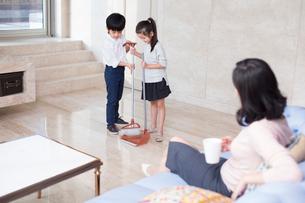 Happy Chinese siblings sweeping in the living roomの写真素材 [FYI02226693]