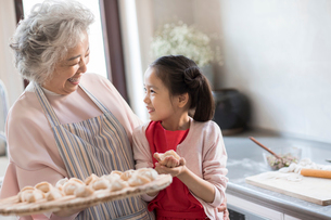 Cheerful Chinese granddaughter and grandmother making dumplings in kitchenの写真素材 [FYI02226696]