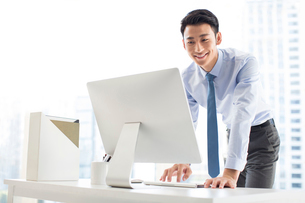 Young Chinese businessman using computer in officeの写真素材 [FYI02226708]