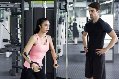 Young woman working with trainer at gymの写真素材 [FYI02226728]