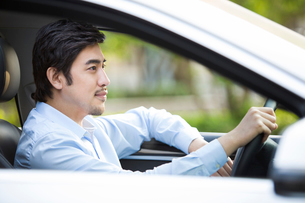 Young man driving carの写真素材 [FYI02226744]