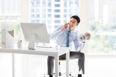 Young Chinese businessman exercising in officeの写真素材 [FYI02226764]