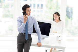 Young Chinese businessman talking on cell phone in officeの写真素材 [FYI02226790]