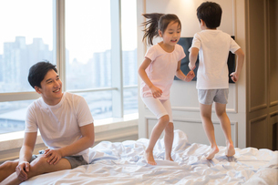 Cheerful young Chinese family having fun on a bedの写真素材 [FYI02226795]