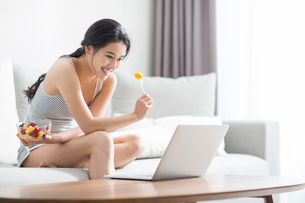 Young woman using laptop at homeの写真素材 [FYI02226802]