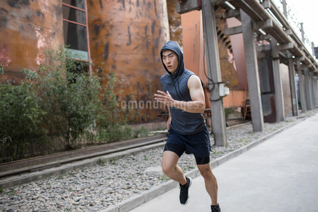 Young Chinese man jogging outdoorsの写真素材 [FYI02226817]