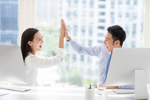 Confident Chinese business people high fiving in officeの写真素材 [FYI02226821]