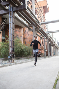 Young Chinese man jogging outdoorsの写真素材 [FYI02226843]