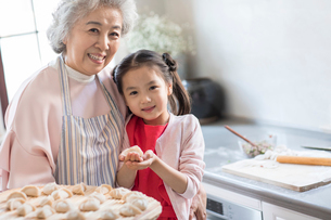Cheerful Chinese granddaughter and grandmother making dumplings in kitchenの写真素材 [FYI02226848]