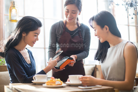 Chinese friends paying with smart phone in cafeの写真素材 [FYI02226875]