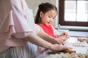 Cheerful Chinese granddaughter and grandmother making dumplings in kitchenの写真素材 [FYI02226886]