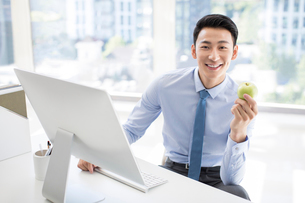 Young Chinese businessman holding an apple in officeの写真素材 [FYI02226917]
