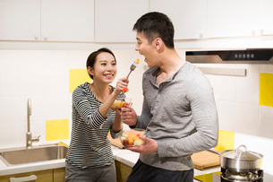 Happy young couple eating fruit salad in kitchenの写真素材 [FYI02226928]