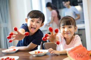 Happy siblings and cherry tomatoesの写真素材 [FYI02226959]