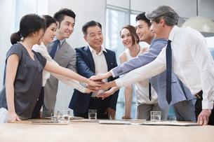Confident business people stacking hands in meeting roomの写真素材 [FYI02227007]