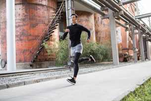 Young Chinese man jogging outdoorsの写真素材 [FYI02227010]