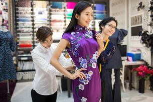 Chinese fashion designers adjusting customer's dressの写真素材 [FYI02227019]
