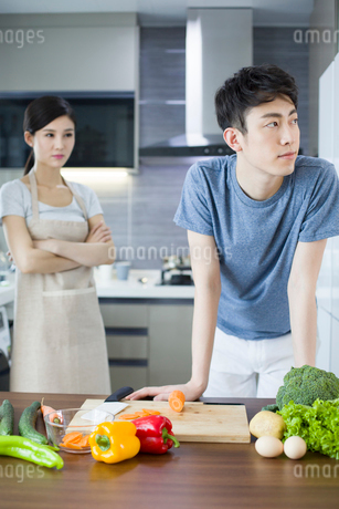 Young couple ignoring each other in kitchenの写真素材 [FYI02227024]