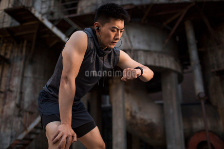 Young Chinese man checking smart watch after runningの写真素材 [FYI02227032]