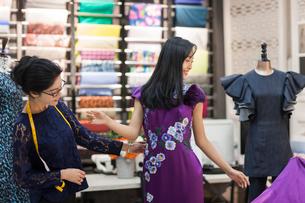 Chinese fashion designer examining dress on customerの写真素材 [FYI02227053]