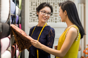 Chinese fashion designer helping customer choosing fabric swatchの写真素材 [FYI02227058]