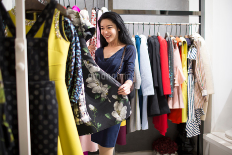 Young Chinese woman shopping in clothing storeの写真素材 [FYI02227059]