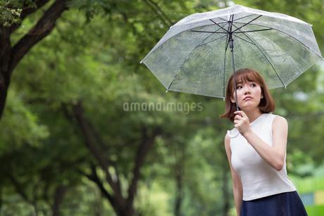Sullen young woman holding umbrellaの写真素材 [FYI02227084]