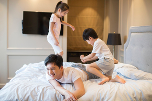 Cheerful young Chinese family having fun on a bedの写真素材 [FYI02227085]