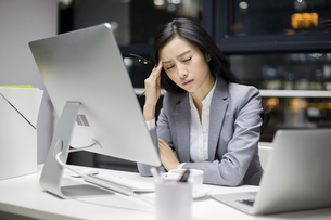 Businesswoman working late in officeの写真素材 [FYI02227116]