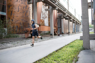 Young Chinese man jogging outdoorsの写真素材 [FYI02227127]