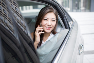 Confident businesswoman talking on cell phone inside carの写真素材 [FYI02227130]