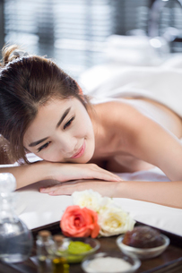 Beautiful young woman relaxing on massage tableの写真素材 [FYI02227136]