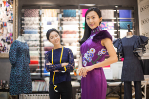 Chinese fashion designer examining dress on customerの写真素材 [FYI02227143]