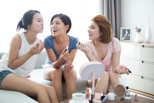 Best female friends applying make-up at homeの写真素材 [FYI02227192]