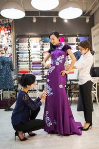 Chinese fashion designers adjusting customer's dressの写真素材 [FYI02227209]