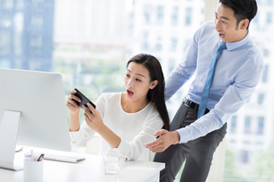Young Chinese business people playing mobile game in officeの写真素材 [FYI02227227]