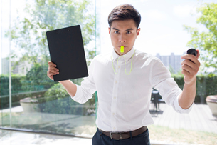 Young businessman blowing whistleの写真素材 [FYI02227239]