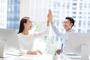 Confident Chinese business people high fiving in officeの写真素材 [FYI02227248]
