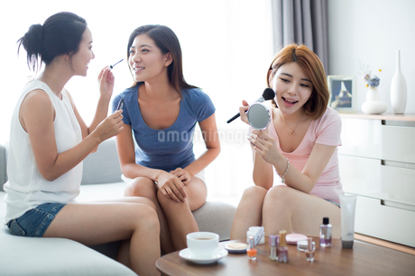 Best female friends applying make-up at homeの写真素材 [FYI02227272]