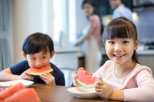 Happy siblings eating watermelonの写真素材 [FYI02227293]
