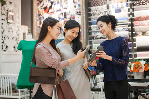 Chinese friends paying with smart phone in clothing storeの写真素材 [FYI02227296]