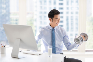Young Chinese businessman exercising in officeの写真素材 [FYI02227326]