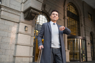 Confident Chinese businessman in travel checking the timeの写真素材 [FYI02227343]