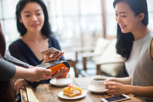 Chinese friends paying with smart phone in cafeの写真素材 [FYI02227363]