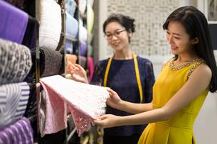 Chinese fashion designer helping customer choosing fabric swatchの写真素材 [FYI02227374]