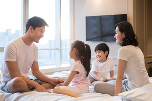 Cheerful young Chinese family having fun on a bedの写真素材 [FYI02227392]