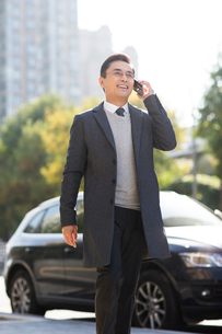 Confident Chinese businessman talking on the phoneの写真素材 [FYI02227423]